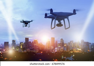 Drones (Multi-rotor) silhouette flying above the city panorama at night scene to find something with spotlight.