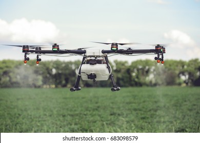 Drones spraying pesticides to grow potatoes. Industrial agriculture and smart farming concept.