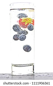 drop blueberries and strawberries in a glass full of sparkling water - close up on the isolated glass