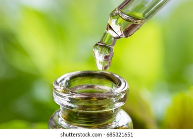 A drop of essential oil is being dropped into a bottle