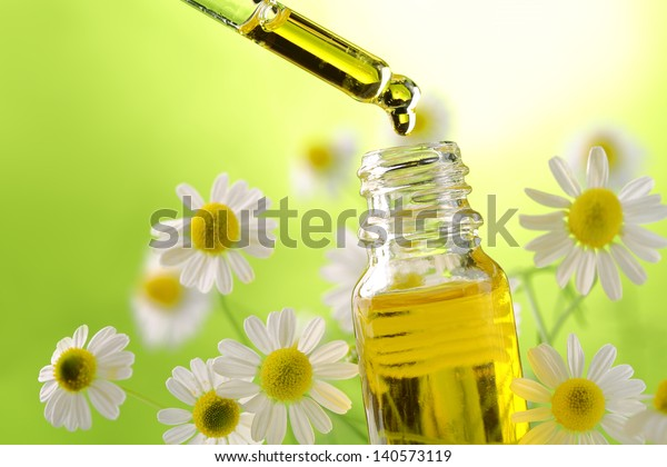 Drop falling from dropper of essential oil, aromatherapy essence, or medicinal liquid