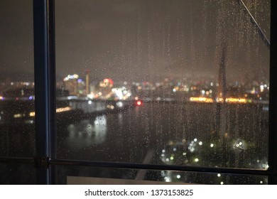 Drop of rain on Tempozan Giant Ferris Wheels window. Background is city and street bokeh out of focus around Aji river in Osaka, Japan.