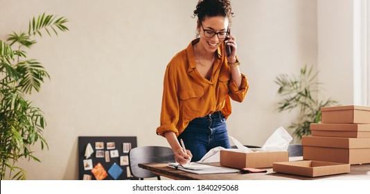 Drop shipping business owner talking on mobile phone and taking order. Female entrepreneur working at home office confirming the order on phone.