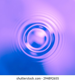 Drop of water hitting a calm colored surface