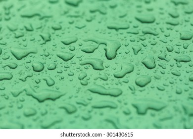 Drop water rain on the green car in close up background and textures