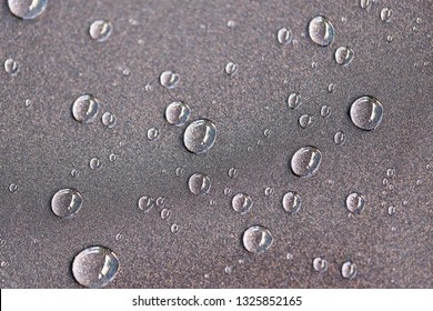 Droplet on the car hood. Water beading after rain or car wash on shiny metallic gray paint surface. Beading created by ceramic coat or paint sealant with high surface tension. Water drop Backgroud.