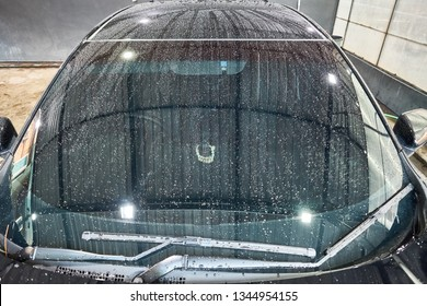 Droplet on the car hood & windshield. Water beading after rain or car wash on shiny black  paint surface. Beading created by ceramic coat or paint sealant with hydrophobic effect. Water drop Backgroud
