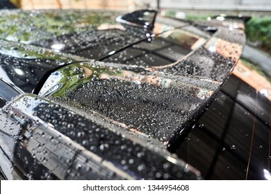 Droplet on the car spoiler & windshield. Water beading after car wash or rain on shiny black  paint surface. Hydrophobic effect created by ceramic coat or paint sealant . Water drop Backgroud.
