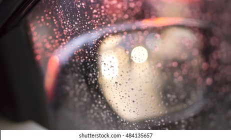 Droplets and car lights reflections through foggy car window