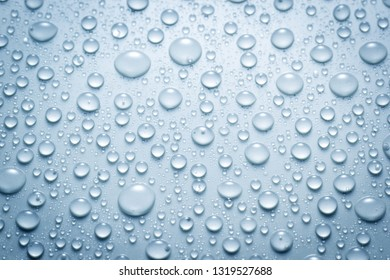 Droplets of water on blue surface, abstract background