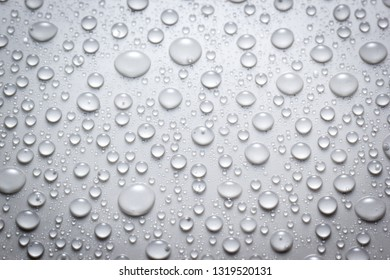 Droplets of water on grey and white surface