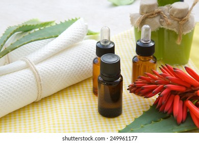 A dropper bottle of aloe vera essential oil. White towels and other spa products in the background