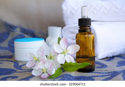 A dropper bottle of apple blossoms extract and apple blossoms on a sack cloth. Cream box,body lotion,white towels in the background