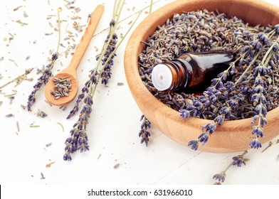 Dropper bottle of aromatic essential oil in wooden bowl full of dried purple lavender herb
