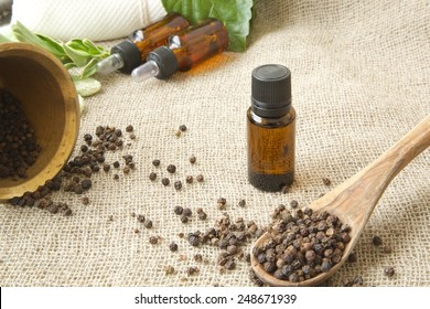 A dropper bottle of black pepper essential oil. Black pepper in the background.