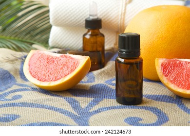 A dropper bottle of grapefruit essential oil. Grapefruits in the background.