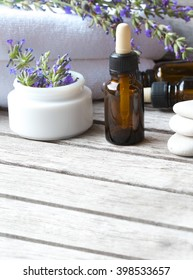 A dropper bottle with lavender essential oil on a old wooden surface. Lavender twig and white towels in the background.