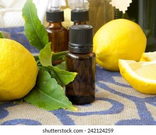 A dropper bottle of lemon essential oil.Fresh lemons in the background