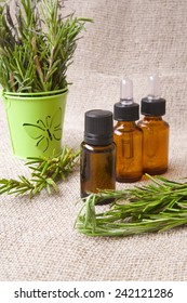 A dropper bottle of rosemary essential oil. Rosemary twigs in a green decorative bucket in the background.