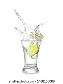 Dropping of lime into glass with tasty tequila on light background