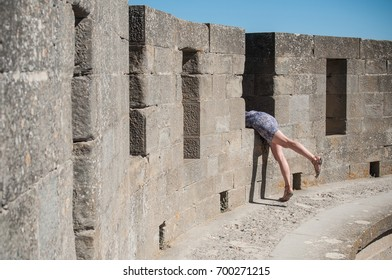 dropping woman taking risk for picture in medieval fortifications in Carcassonne in France