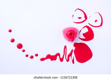 Drops and blots of red color from spilled nail polish on a white background