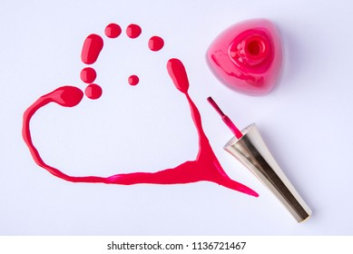 Drops and blots in the shape of a heart of red color from spilled nail polish on a white background