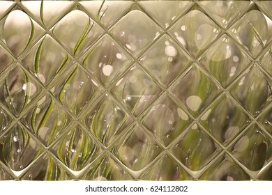 The drops of dew on the grass through window panes