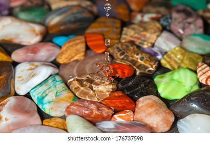 drops falling into shallow water, multicolored stones at the bottom