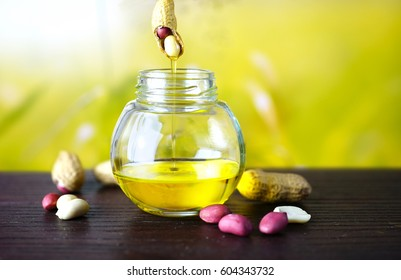 Drops of oil drain off peanut into a round jar. Peanuts scattered on a wooden table on a light green and yellow blur background .