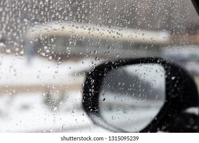 Drops on a glass. Rear-view mirror located behind a glass with drops.