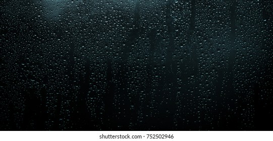 Drops on the window glass in the night,silhouettes of drops