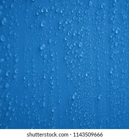 Drops of rain background texture on blue glass background / drops on glass after rain