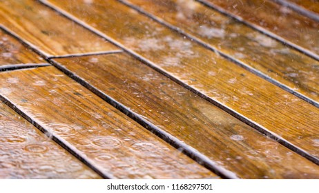 drops of rain fall on a wooden terrace and a bridge near the pool