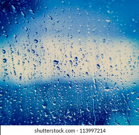 Drops of rain on blue glass background / drops on glass after rain