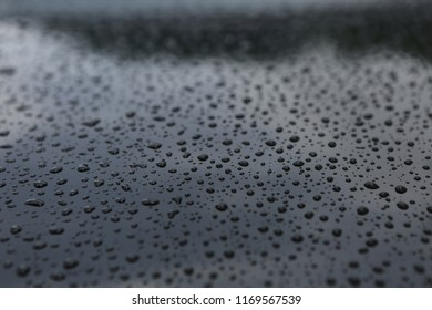 drops of rain on the hood of a black car with a reflection of the sky