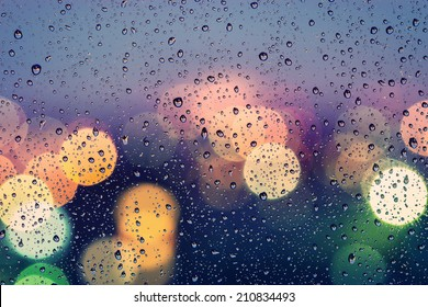 Drops of rain on window with abstract bokeh lights