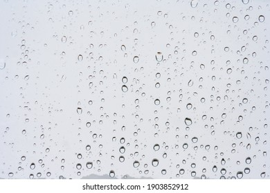 Drops of rain on the window or glass. Gray wet glass pattern texture. Abstract backgrounds