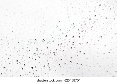 Drops of rain on window glass background. Bokeh lights out of focus. Abstract Backdrop