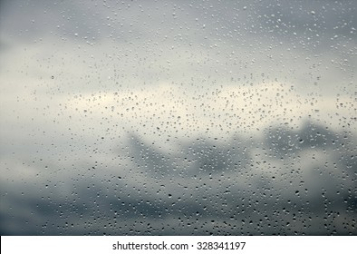 Drops of rain on a window glass.Through the window view of the sea and overcast clouds