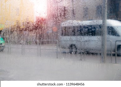 Drops of water flow down the windowpane. Waking the weather outside the window. Cars drive on a wet road. Abstract background