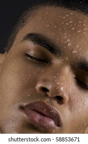 Drops of the water on face of a young man on black background.