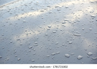 Drops of water on the hood of a car with sky and clouds reflection