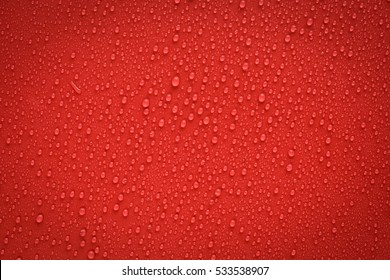 Drops of water on red and black surface. Macro photo, drop, shadow plastic base.