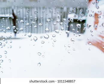Drops of water on the window. Snow outside the window.