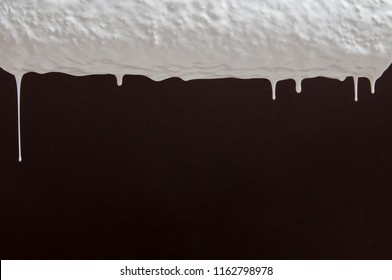 drops of white paint flow down from the roller on a dark background