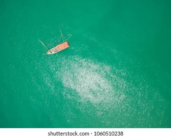 Dropshot of fishing boat on emerald tropical sea