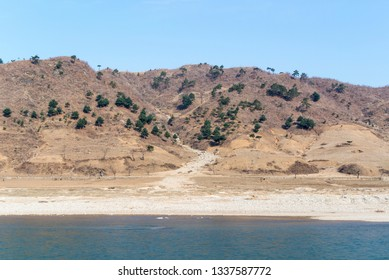 Drought ridden barren spring landscape in North Korea with river in the foreground