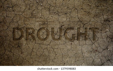 Drought text over dry and cracked brown dirt