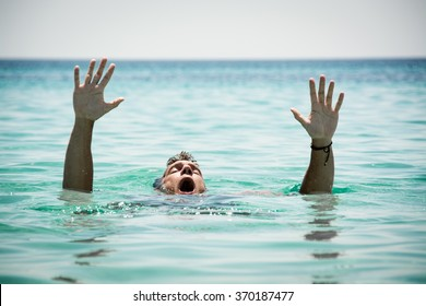 Drowning man in sea asking for help with raised arms.